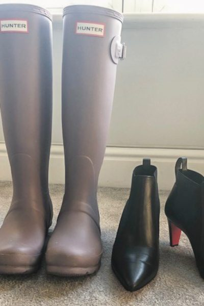 A pair of Hunter wellies sits next to a pair of black Louboutin heeled boots.